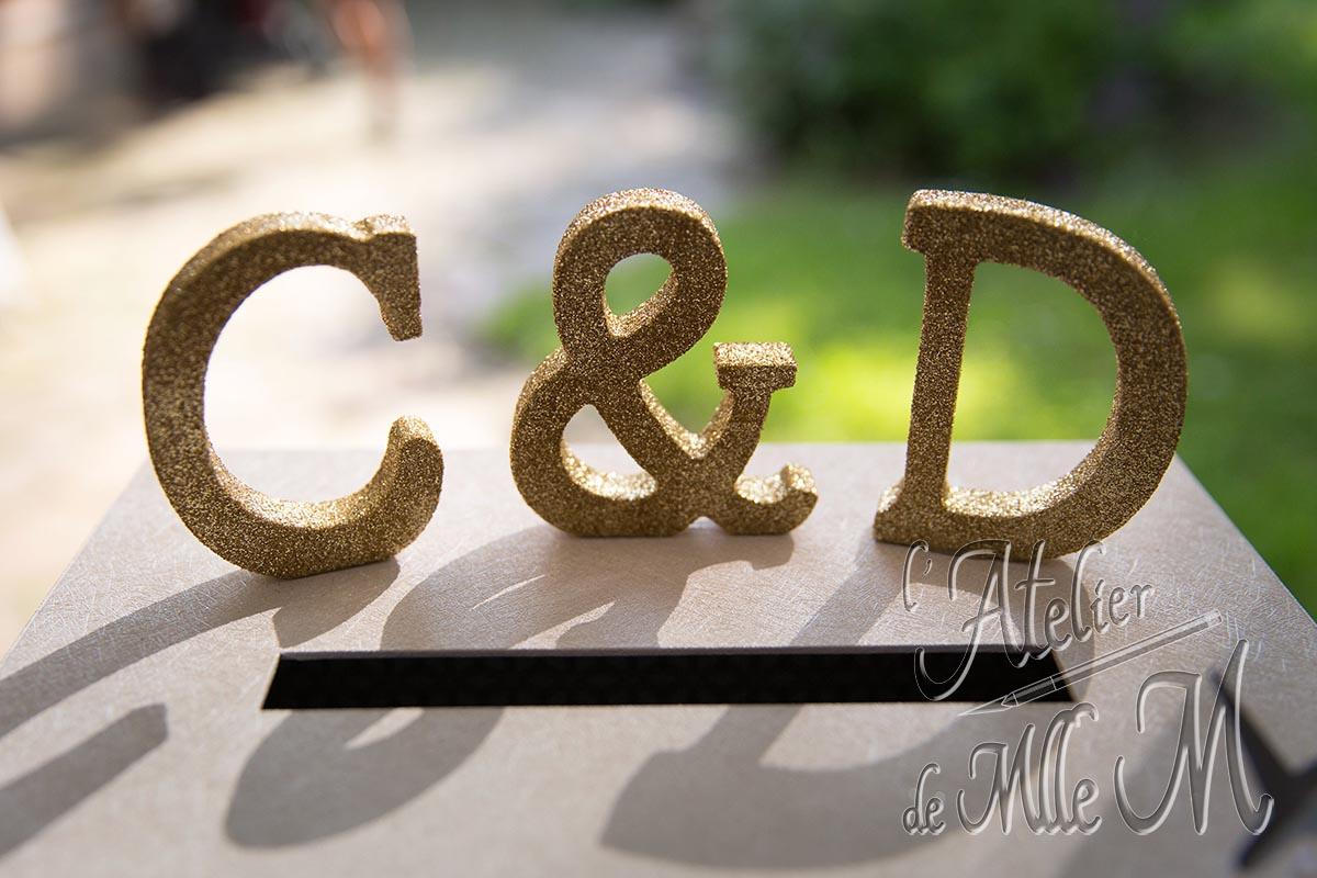 Lettres pailletées décorant l'urne de mariage 3 valises. Composition : Lettres en bois pailleté manuellement.