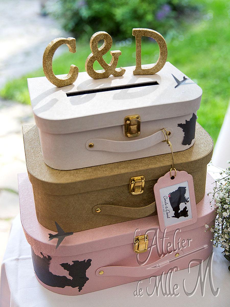 Urne de mariage composée de 3 valises superposées sur la thématique du voyage. L'article dédié à cette création sur le Blog : https://www.latelierdemllem.com/urne-mariage/ Composition : Carton – Papier Skivertex. Attaches parisiennes – Boucles métalliques dorées. Papiers décoratifs – Strass. Dimensions : 33 (H) x 37 (l) x 23 (P) cm.