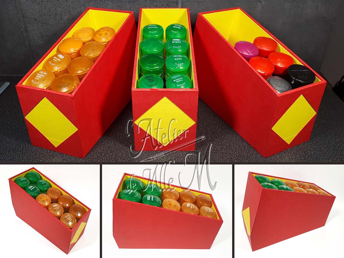 Des rangements à épices fait sur mesure pour poser sur les étagères d'un placard de cuisine. Composition : Carton – Papiers cadeaux. Dimensions : 17,5 (H) x 25 (P) x 9,7 (l) cm.