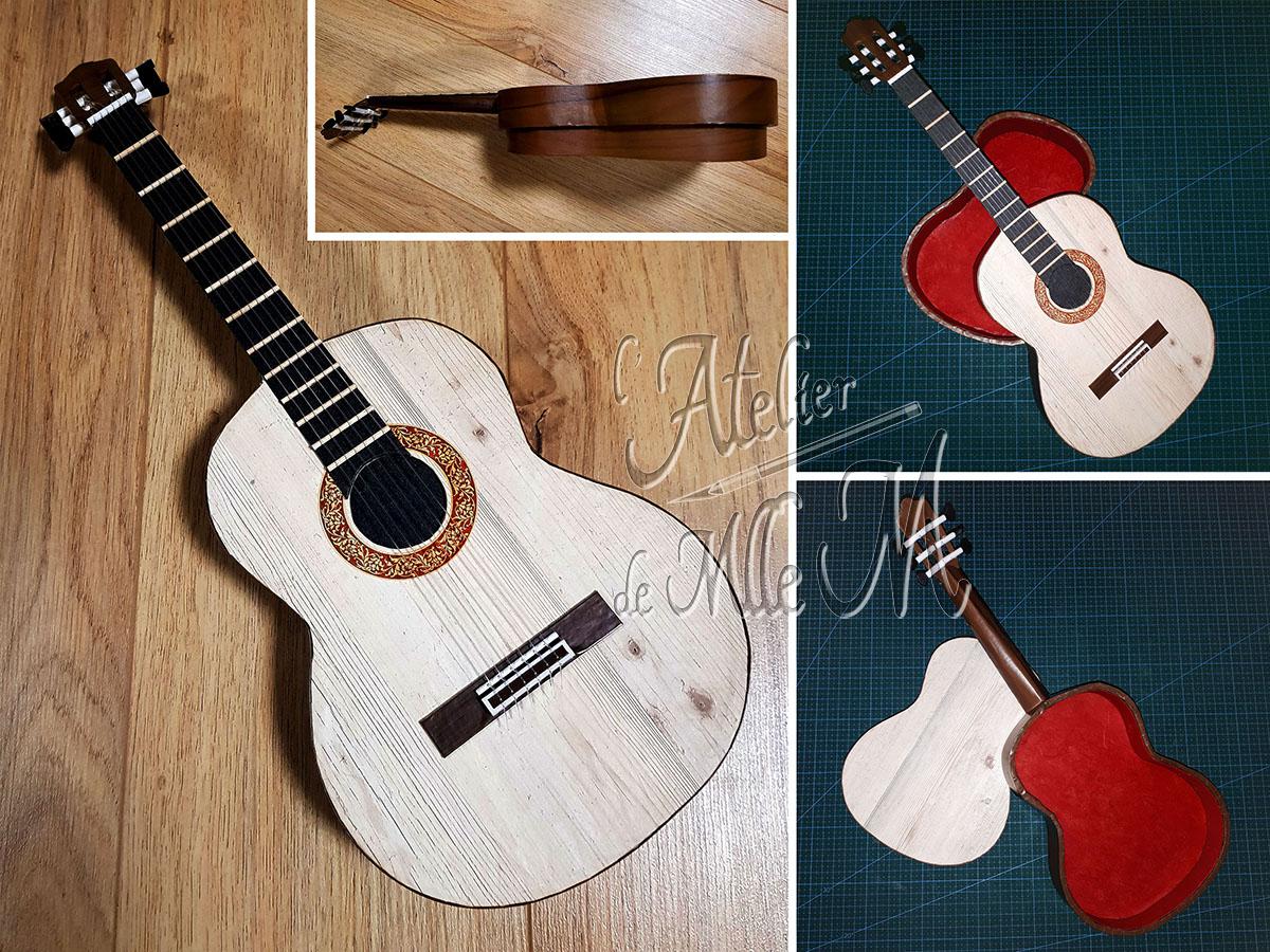 Ne dirait-on pas une vraie guitare miniature ?! Eh bien non, il s'agit bel et bien d'une boîte en carton customisée pour être la plus réaliste possible. Composition : Carton – Papiers de décoration et imitation bois. Cure-dents – Fils de nylon. Dimensions : 10 (H) x 40 (L) x 15 (l) cm.
