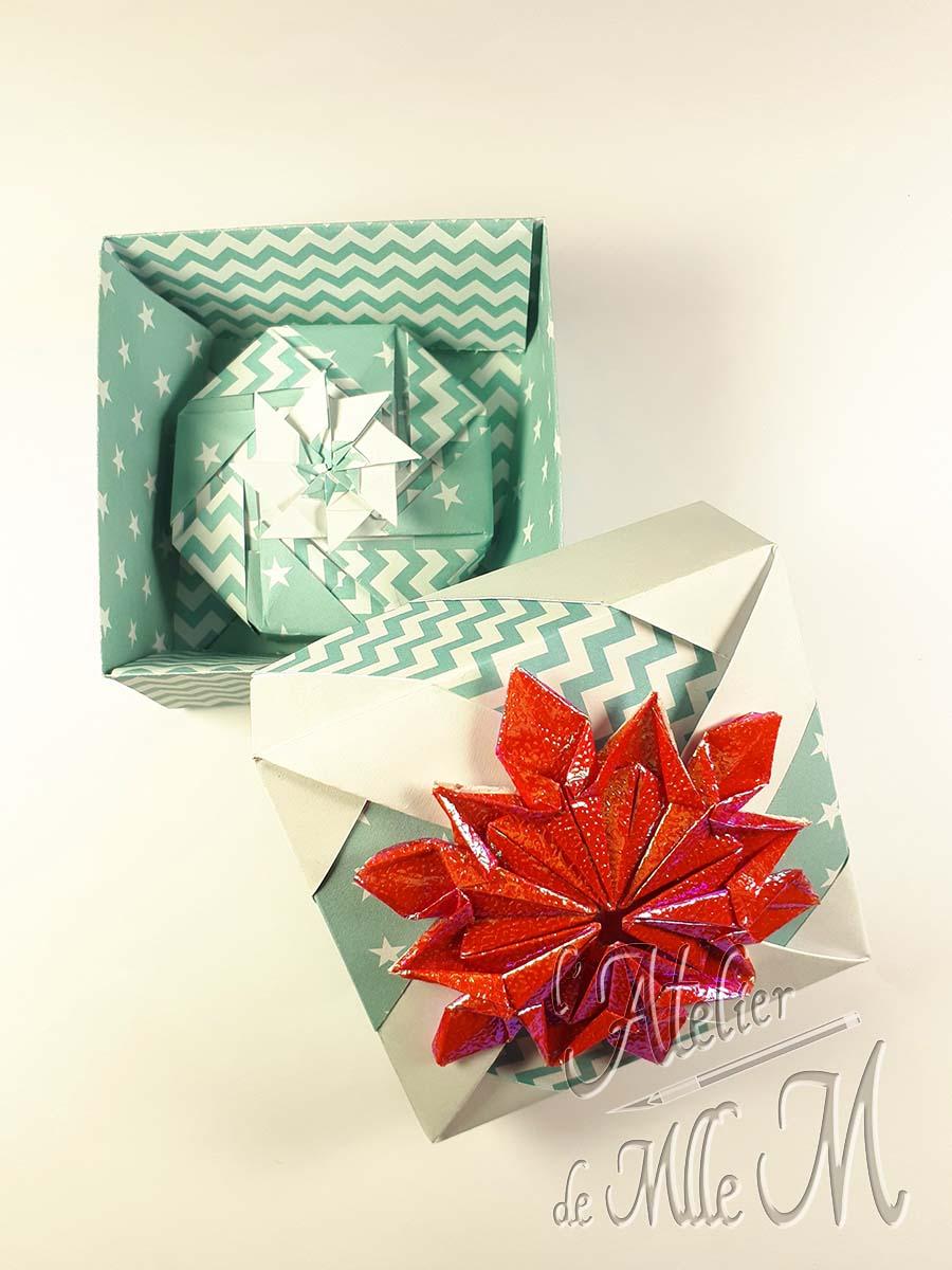 Deux boîtes origamis s'emboitant, décorées par un flocon de neige origami iridescent.